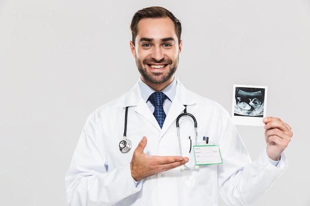 Портрет кавказского молодого врача, работающего в больнице и держащего ультразвуковое сканирование ребенка, изолированного над белой стеной