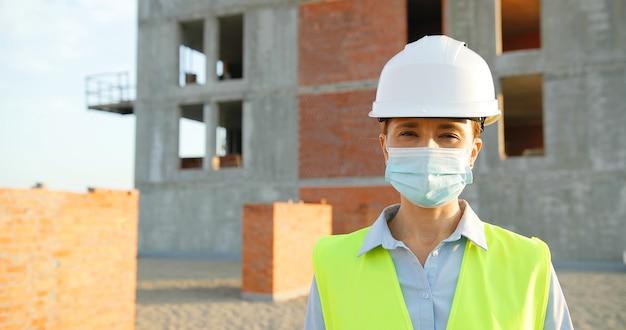 建設時に屋外に立ってカメラを見ているカスクと医療マスクの白人の若いきれいな女性コンストラクターの肖像画。ヘルメットの建物で女性ビルダーのクローズアップ。コロナウイルス。