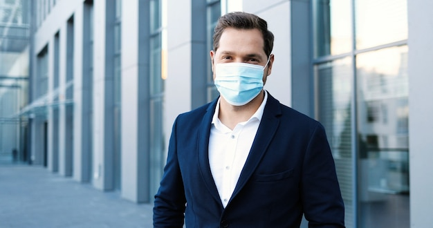 カメラを見て、笑顔で都会の通りに立っている医療マスクの白人の若いスタイリッシュなビジネスマンの肖像画。コロナウイルスパンデミックの間にビジネスセンターで都市の屋外の男性。