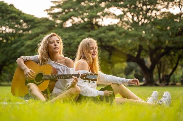 Портрет кавказских молодых женщин, сидящих в парке на открытом воздухе и играющих на гитаре, поют песню вместе от счастья