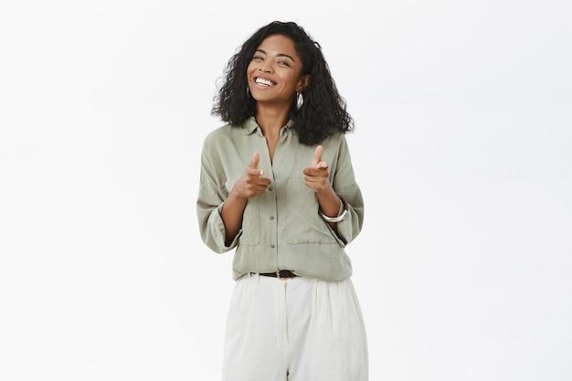 カリスマ的なフレンドリーで明るい魅力的な浅黒い肌の若い女性のブラウスとズボンを指で指している肖像画