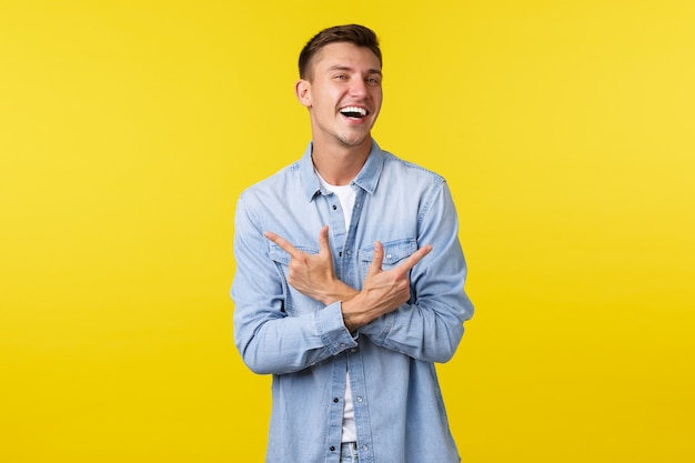 카리스마 넘치는 금발 남자의 초상화는 행복하게 웃고 손가락을 옆으로 가리키며 왼쪽 및 오른쪽 변형 또는 제품을 보여주며 노란색 배경 위에 쾌활하게 서 있습니다.