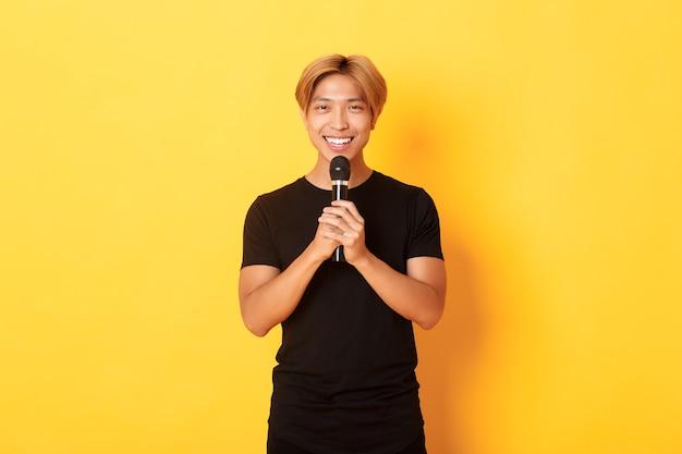 Портрет харизматичного улыбающегося азиатского мужчины, держащего микрофон и поющего караоке