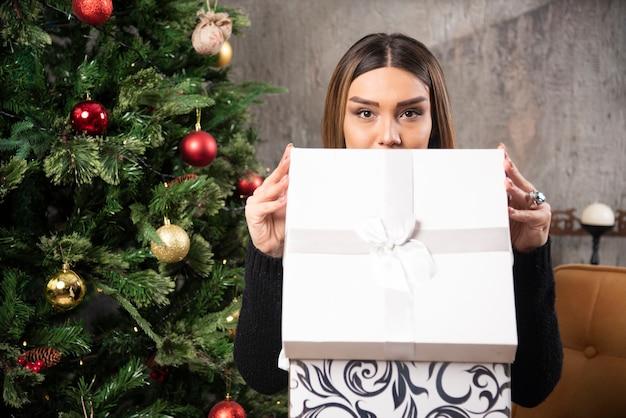 座ってクリスマスプレゼントを開くカリスマ的な女性の肖像画。高品質の写真