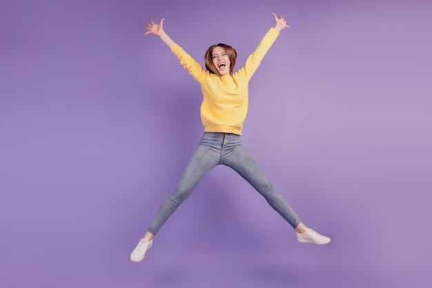 Портрет очаровательной активной энергичной смешной леди прыгает, развлекается на фиолетовом фоне