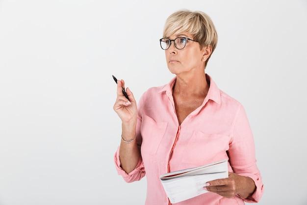 Портрет очаровательной взрослой женщины в очках, держащей учебную книгу и ручку, изолированную над белой стеной в студии