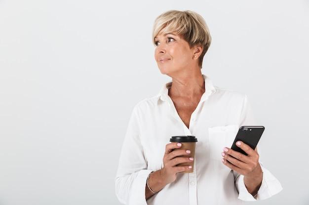 スタジオで白い壁の上に分離された携帯電話とテイクアウトのコーヒーカップを保持している短いブロンドの髪を持つ魅力的な大人の女性の肖像画
