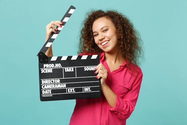 파란색 청록색 배경에 격리된 클래식 블랙 필름 제작 클래퍼보드를 들고 평상복을 입은 매력적인 아프리카 소녀의 초상화. 사람들은 진심 어린 감정 라이프 스타일 개념입니다. 복사 공간을 비웃습니다.