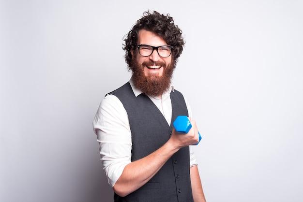 Портрет очаровательного и забавного бородатого мужчины в сером костюме, работающего с синей маленькой гантелью