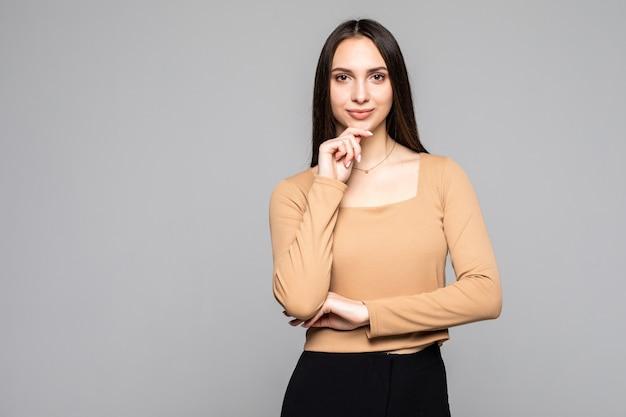 Портрет очаровательной и милой молодой женщины смотрит в сторону, держа руку на подбородке, изолированной на серой стене с местом для текста