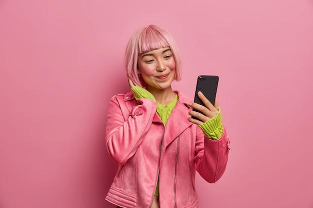 매력적인 아시아 소녀의 초상화는 스마트 폰에서 셀카를 찍고 패션 블로그를 위해 자신의 사진을 만들고 분홍색 헤어 스타일을 가지고 긍정적으로 미소 짓습니다.