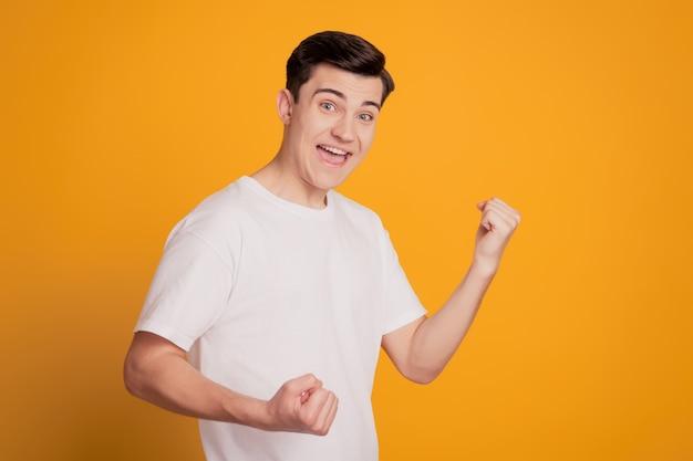 매력적인 놀란 남자 입을 벌린 초상화는 노란색 배경에 주먹 승자 개념을 올립니다