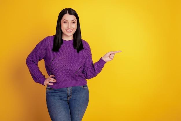 Портрет очаровательной привлекательной веселой великолепной очаровательной девушки указывает пальцем на пустое пространство, изолированное на желтом цветном фоне
