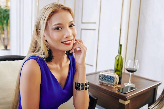 Restauranr에서 레드 와인을 마시는 금발 머리를 가진 매력적인 매력적인 젊은 아시아 여자의 초상화