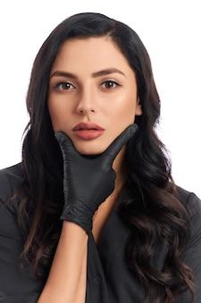 Портрет очаровательной косметолога в черной униформе и перчатках позирует на белом