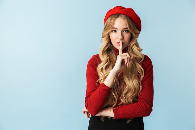 서있는 동안 입에 손가락을 잡고 빨간 베레모를 입고 매력적인 금발 여자 20 대의 초상화, 절연