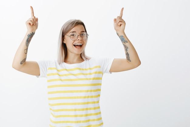 スタジオでポーズをとってメガネで魅力的なブロンドの女の子の肖像画