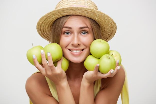 白い背景の上にポーズをとって、広い笑顔で元気にカメラを見て、上げられた手でリンゴを保持しているカンカン帽の魅力的な青い目の若いブロンドの女性の肖像画