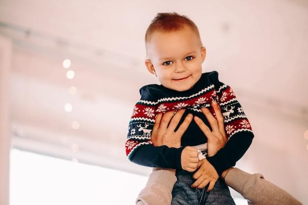 正面に笑顔の冬のパターンとセーターの魅力的な男の子の肖像画