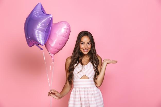 ピンクの壁に隔離された2つの風船を笑顔で保持しているドレスを着て長い髪の魅力的なブルネットの少女20代の肖像画