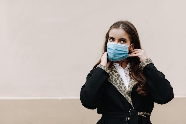 屋外に立って医療衛生マスクを身に着けている魅力的なブルネットの肖像画。通りでポーズをとって、感染症から身を守る若い女性。