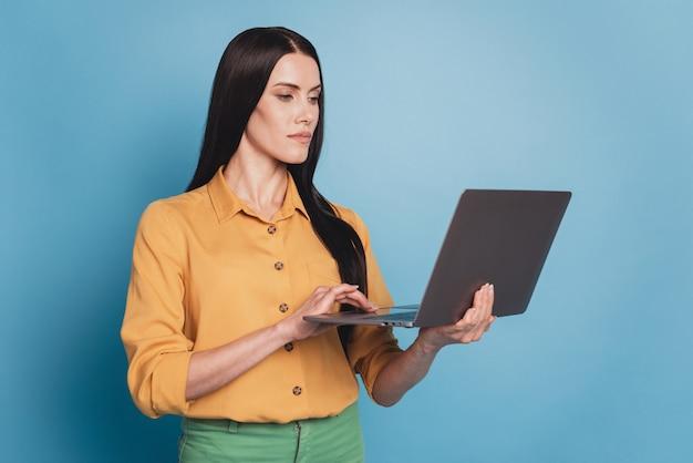青い背景にネットブックと魅力的な実業家の肖像画
