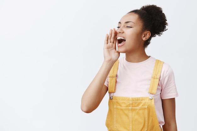 Портрет очаровательной беззаботной городской женщины в модном желтом комбинезоне, поворачивающей налево, держащей ладонь у открытого рта и кричащей