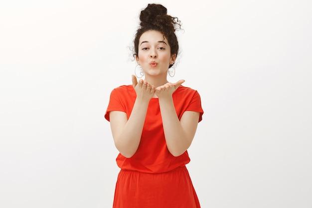 Портрет очаровательной заботливой европейской девушки с вьющимися волосами, зачесанными в пучок, в милом красном платье