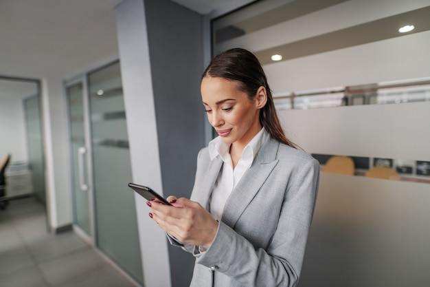Портрет очаровательной кавказской коммерсантки в костюме, стоящей в зале агентства недвижимости и назначающей встречу с клиентами по смартфону.