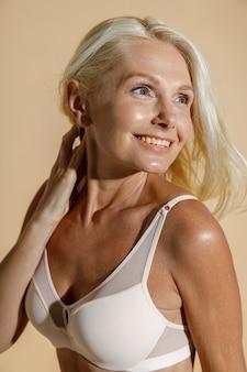 笑顔の白いランジェリーで完璧な肌を持つ魅力的な白人の成熟したブロンドの女性の肖像画