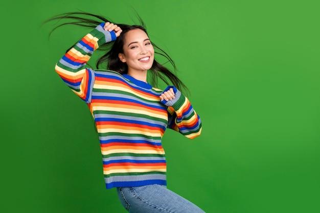 明るい緑色の背景に分離された楽しいパーティータイム風吹く髪を持って踊る魅力的な陽気な女の子の肖像画