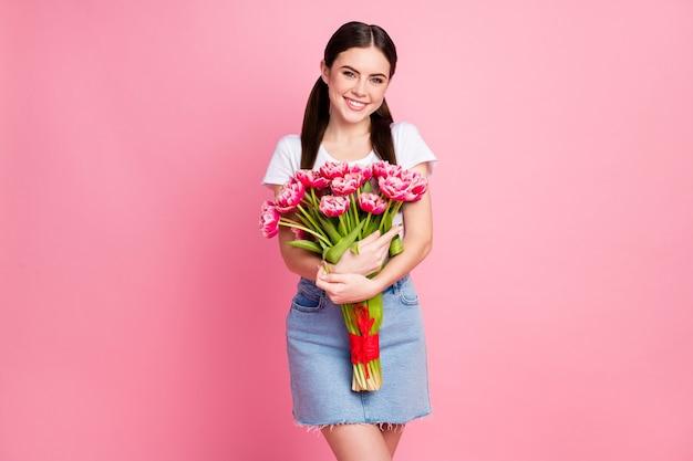 Портрет очаровательной жизнерадостной девушки, держащей в руках букет свежих цветов