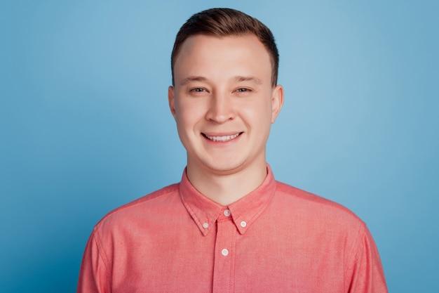 青い背景に魅力的な陽気な男の歯を見せる晴れやかな笑顔の肖像画