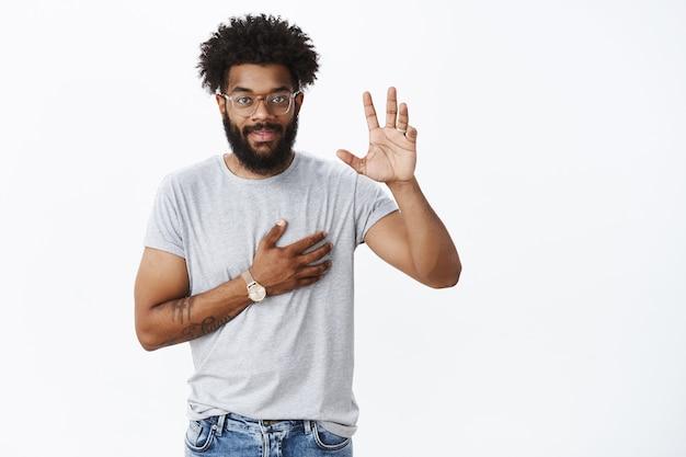 회색 벽 위에 거짓말을 하지 않겠다고 맹세하거나 맹세하면서 손을 들고 팔을 잡고 있는 매력적인 자신감 있고 웃고 있는 아프리카계 미국인 남성의 초상화