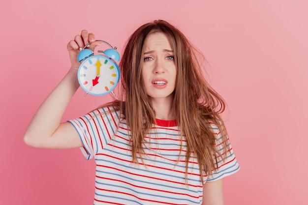 Портрет очаровательной сумасшедшей дамы держит будильник с разочарованным лицом на розовом фоне