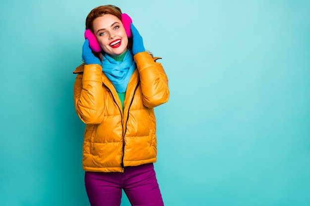 매력적인 귀여운 여자 휴식의 초상화는 터치 부드러운 밝은 귀 머프를 편안하게 착용 캐주얼 스타일의 파란색 바지 분홍색 노란색 옷을 즐길 수 있습니다.