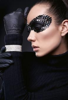 スタジオで黒でポーズをとるタートルネックのセーターとスパンコールマスクの魅力的なエレガントなブルネットの女性の肖像画