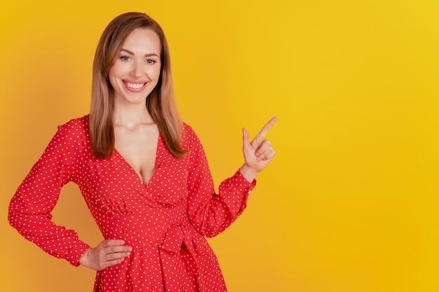 매력적인 우아한 여성의 초상화는 노란 벽에 빈 공간을 직접