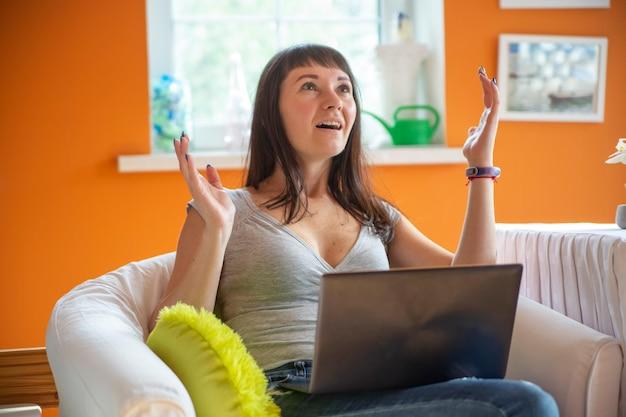 Портрет очаровательной эмоциональной взволнованной нервной женщины с руками, смотрящими на компьютер
