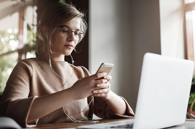 トレンディな髪型のメガネ、ラップトップの近くに座って、イヤホンを着用し、スマートフォンを保持し、メッセージを送信する魅力的なヨーロッパの女性の肖像画。