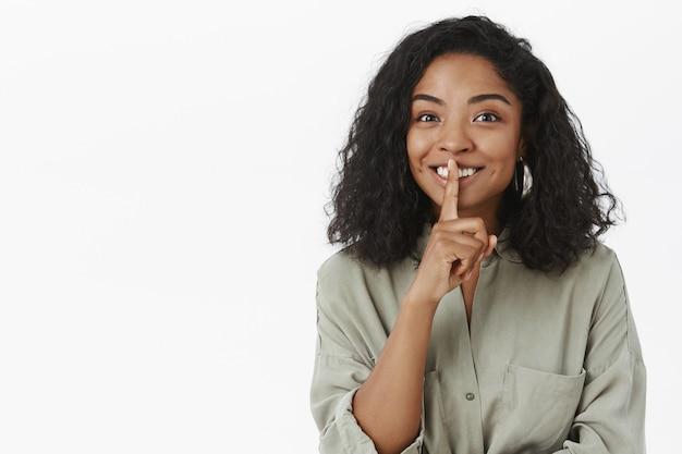 Портрет очаровательной, дружелюбной, восхищенной милой темнокожей женщины с кудрявой прической, молчащей и улыбающейся