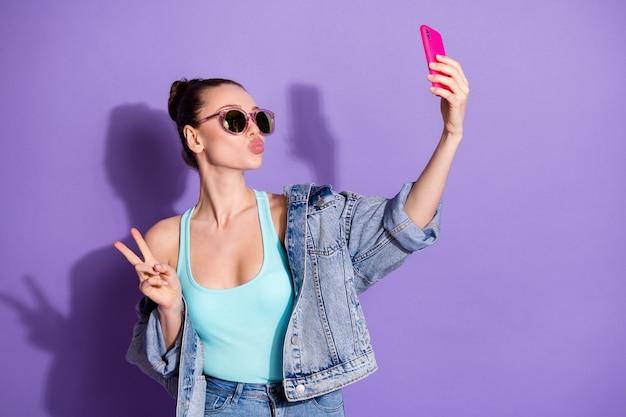 魅力的な女の子のブロガーの肖像画はスマートフォンを使用してフォロワーを購読者にします