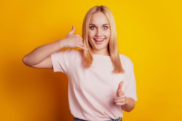 매력적인 소녀 오픈 입 쇼의 초상화 노란색 배경에 제스처 직접 손가락 카메라를 다시 전화
