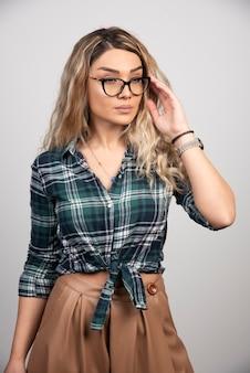 ファッショナブルなメガネをかけている魅力的な女の子の肖像画。