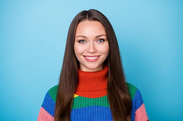 매력적인 소녀의 사랑스러운 소녀의 초상화는 파란색 배경 위에 격리된 카메라 이빨 미소 착용 스타일의 세련된 트렌디한 점퍼에서 멋지게 보입니다.