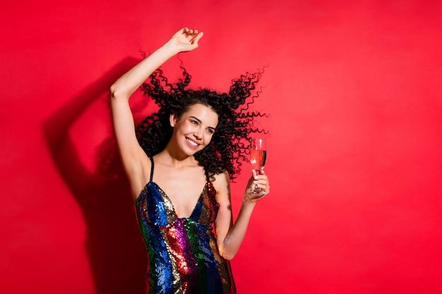 Портрет очаровательной радостной веселой волнистой девушки, пьющей вино, весело отдыхающей, изолированной на ярко-красном цветном фоне
