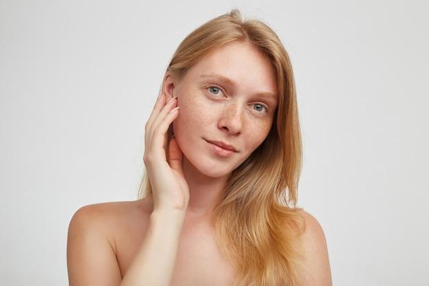 魅力的な緑色の目の若い赤毛の女性の肖像画は、白い壁の上に立って、上げられた手で彼女の頬に優しく触れ、前向きに見ています