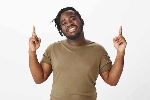 Портрет очаровательного парня в коричневой футболке позирует у белой стены