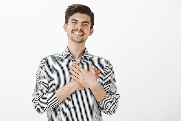 수염과 콧수염을 가진 매력적인 행복 백인 남자의 초상화, 마음에 손바닥을 들고 만족에서 웃고, 좋은 제스처로 감동