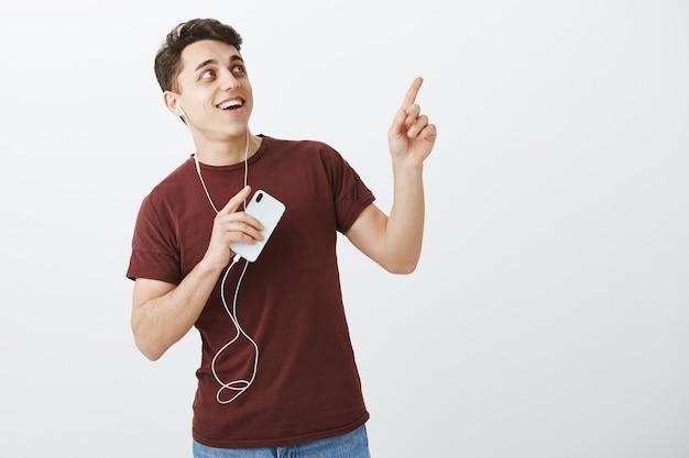 Портрет очаровательного впечатленного привлекательного студента в красной футболке и джинсах
